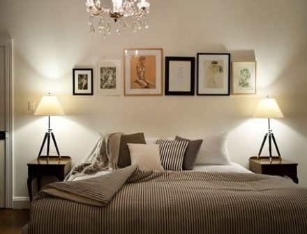 bed with multiple framed pictures above, and 2 lamps