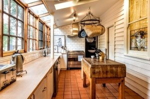 farm style kitchen with wooden benches and white panelled wall