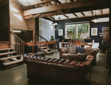 The lounge room at the with leather chairs and exposed wooden beams at The Stables