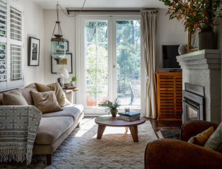 A cute lounge with a fireplace and view of trees out the window at the pet friendly accommodation called Olivie Cottage, Daylesford
